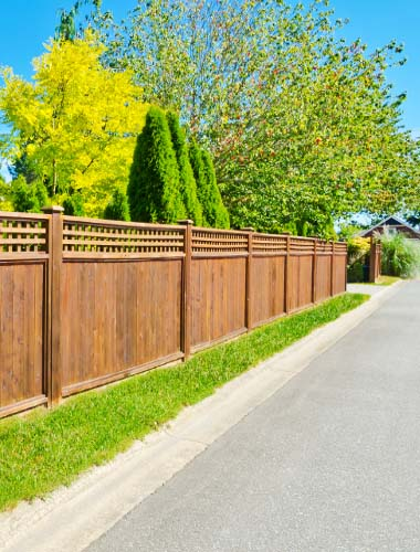 Fence Installation in London made of fencing panels and stained wood along a roadside